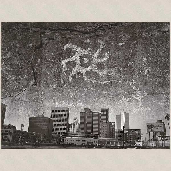 Image of petroglyph superimposed over city